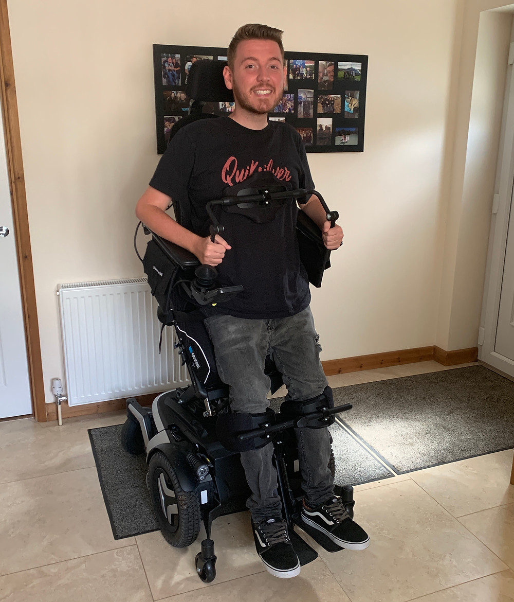 Ross stood up in the f5 vs wheelchair, supported by knee restraints and a chest bar