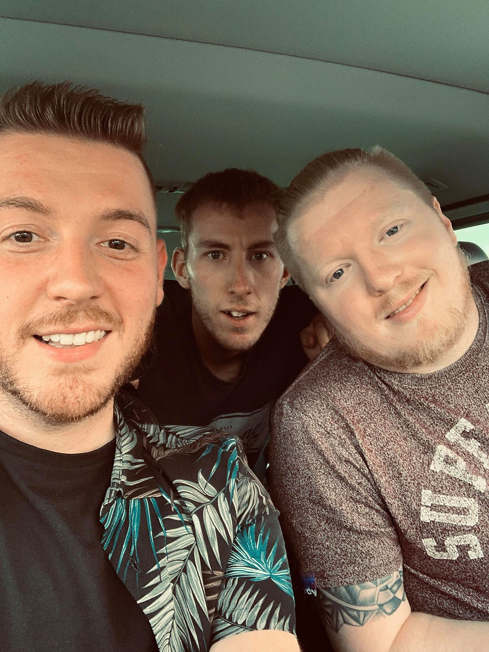 A selfie taken inside the car of Ross and his friends Mark and James