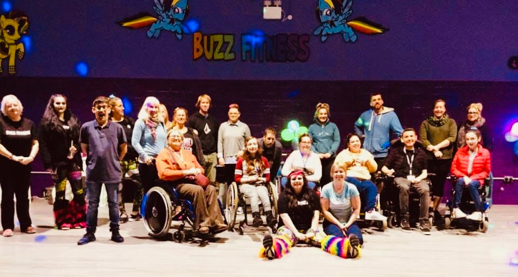 "A group photo of everyone attending the event, underneath the 'Buzz Fitness"" sign"