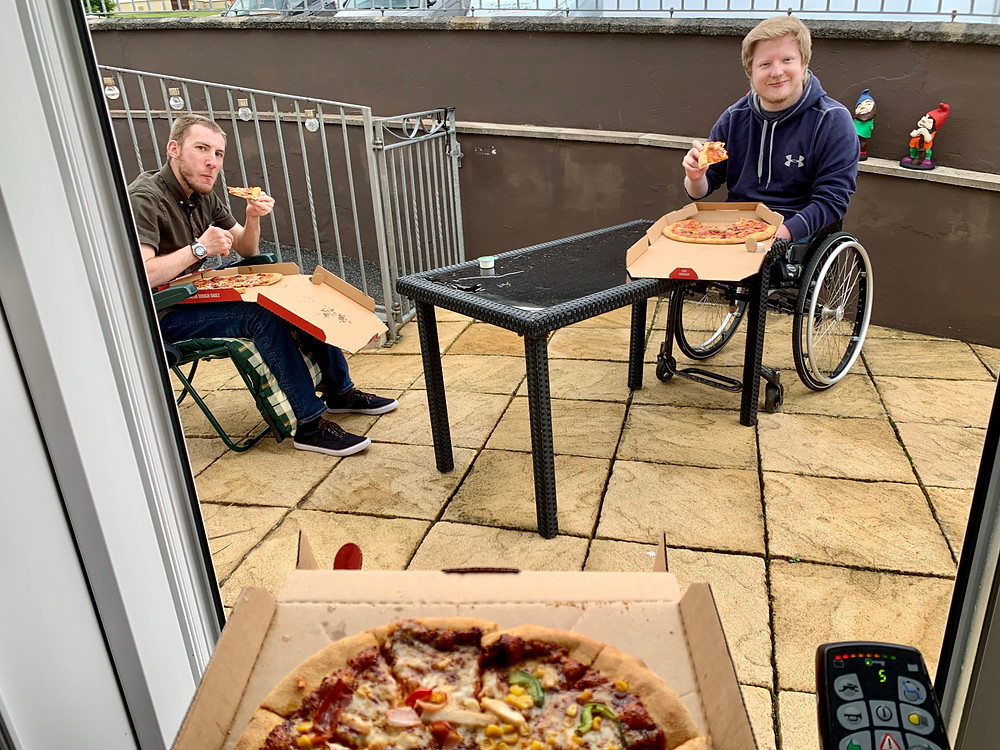 Shot of Ross's friends spaced apart in the garden with pizza boxes on their laps