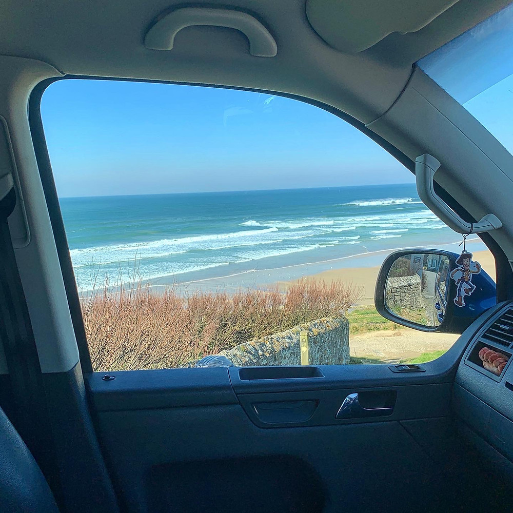 View of the beach through Ross's car window. Bright blue skies and gentle waves