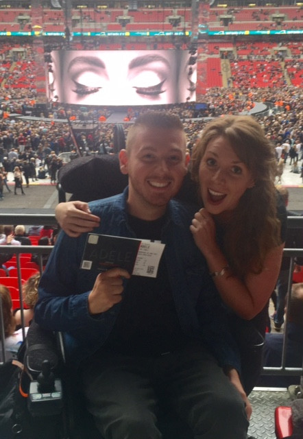 Ross & his sister holding their Adele tickets, with the stage in the background