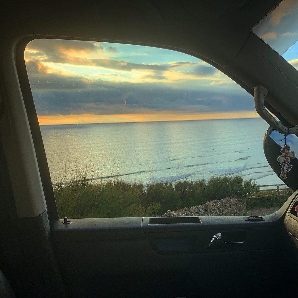 View of the sunset over the beach, from Ross's car window