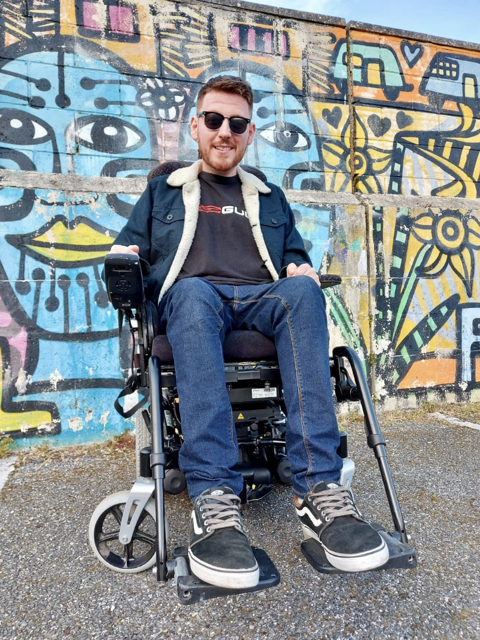 Low down angle of Ross in his wheelchair, sat in front of a multicoloured graffiti wall