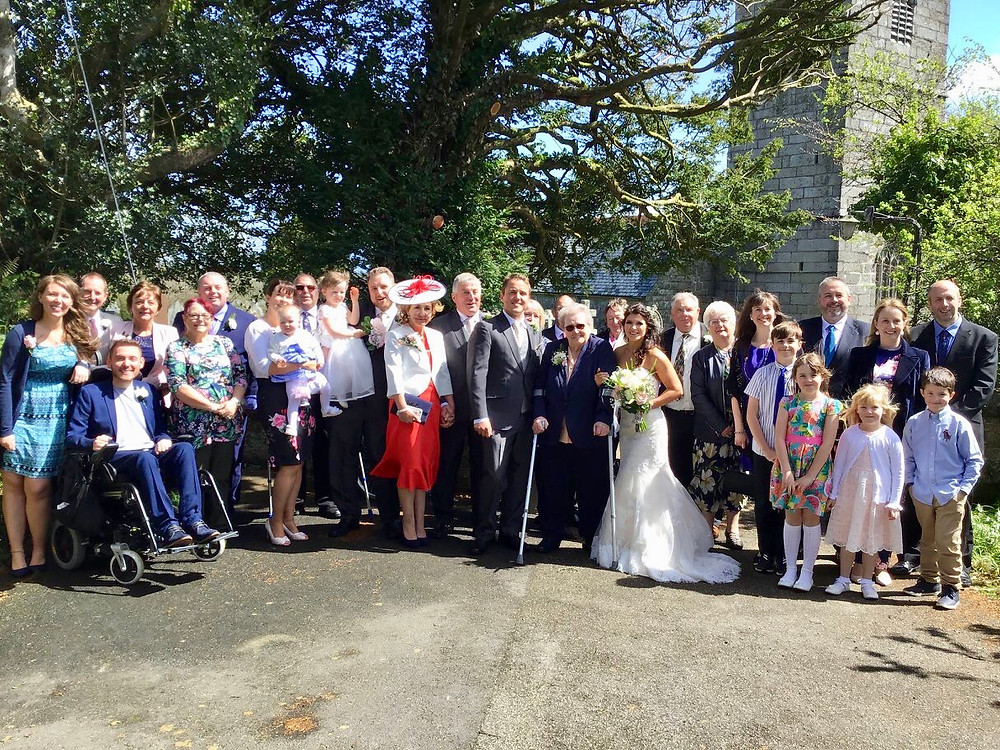 A group shot of the family stood outside the wedding church