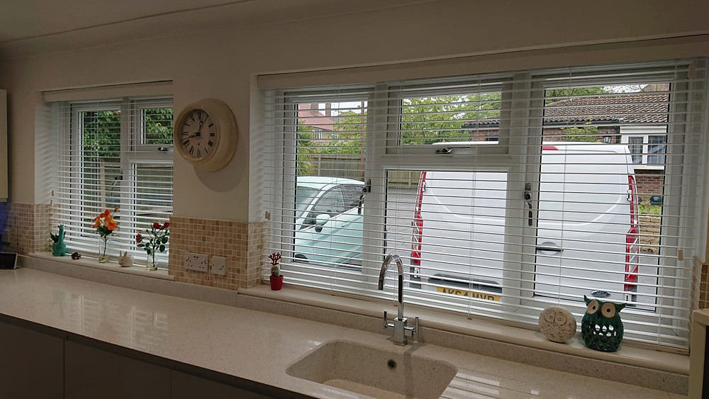 Two windows with white wooden blinds installed.