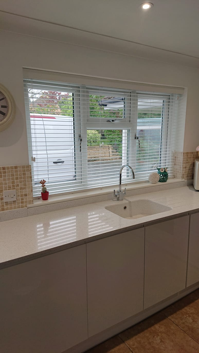 A picture of a new kitchen and white wooden blinds