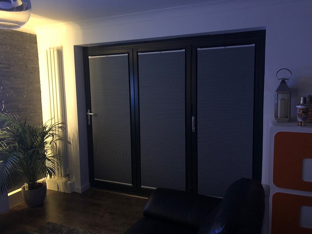 An image of bi fold doors with pleated perfect fit blinds.