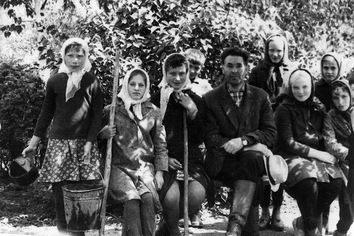Учитель Кондрашов Н.Е. с учащимися Троицкой школы в саду за работой. Фото 1969 г.