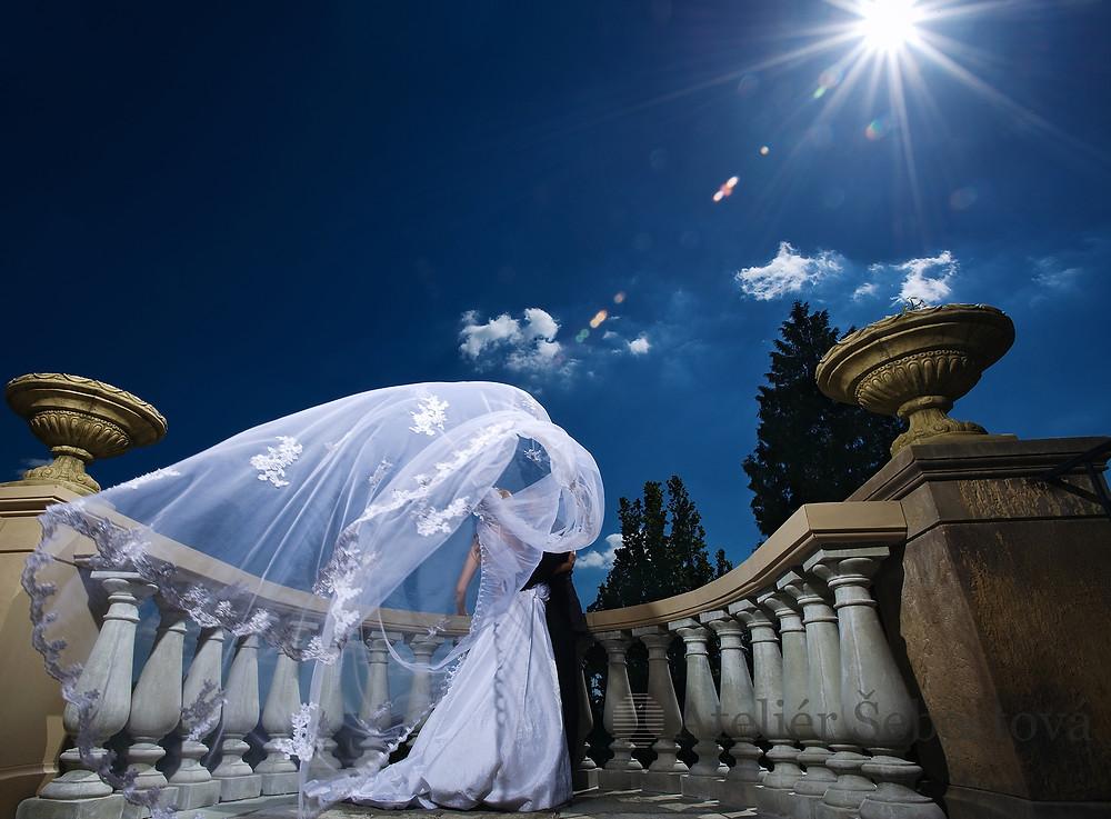 svatební pár pod vlajícím závojem, modré nebe