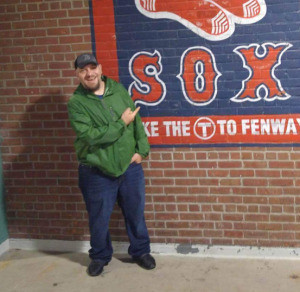 Man in front of Red Sox sign at Fenway