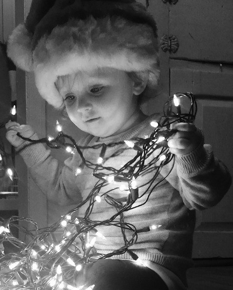 Child playing with Christmas Tree lights