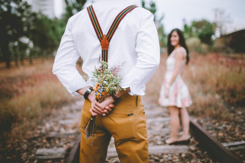 Man hiding flowers behind his back