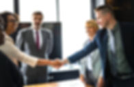 Business Meeting - Fourt people are standing across a table. A woman is greeting with a handshake a man in a suit