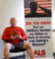 """Roger Brannon is sittig down in a chair, talking. Behind him there is a banner with a USA flag and a saluting soldier. It reads """"Did you know that ou military heroes are twice as likely to develop Lou Gehrig's Desease?"""