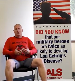 "Roger Brannon is sittig down in a chair, talking. Behind him there is a banner with a USA flag and a saluting soldier. It reads ""Did you know that ou military heroes are twice as likely to develop Lou Gehrig's Desease?"