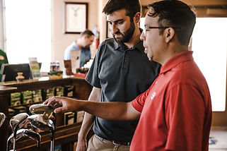 A man is training a new employee at a golf store