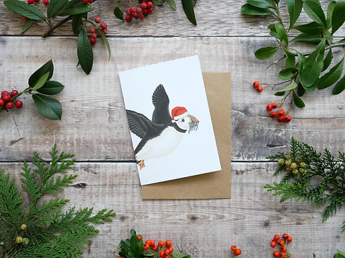 Illustrated flying puffin wearing a santa hat Christmas card made from recycled paper and eco friendly plastic-free wrapper