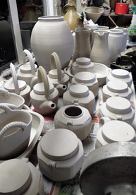Jugs and faceted vases patiently waiting their turn to be bisque fired