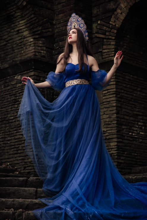 A woman standing in front of a gothic looking building earing a flowing blue dress. She is holding part of the skirt in her  and wearing a crown.