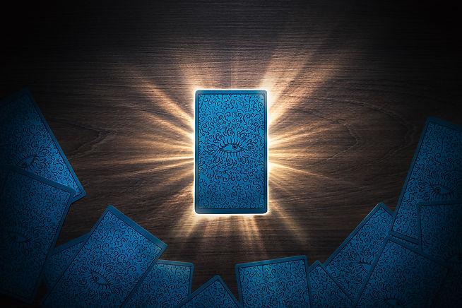 Tarot card facing down on a table with light rays..jpg