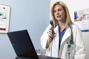 Female physician using a handheld microphone to dictate in front of a laptop.