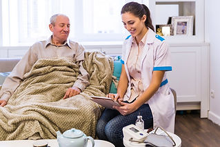 A female nurse looking at a spiral notebook next to an elderly man covered in a blanket.