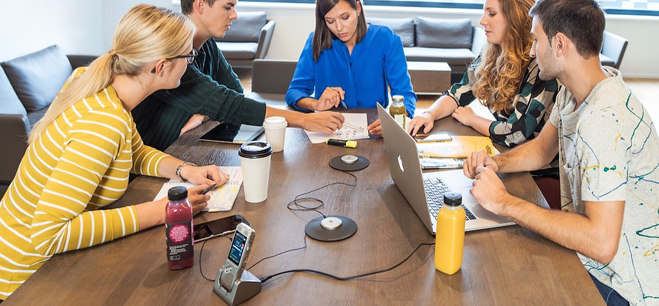 A group of people at a conference room table with a recording device in the middle.
