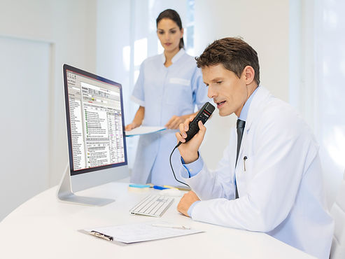 A doctor dictating into a speech mic in front of an EHR with a nurse behind him.