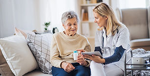 Female nurse with a tablet on a couch with an elderly woman holding a pill bottle and smiling.