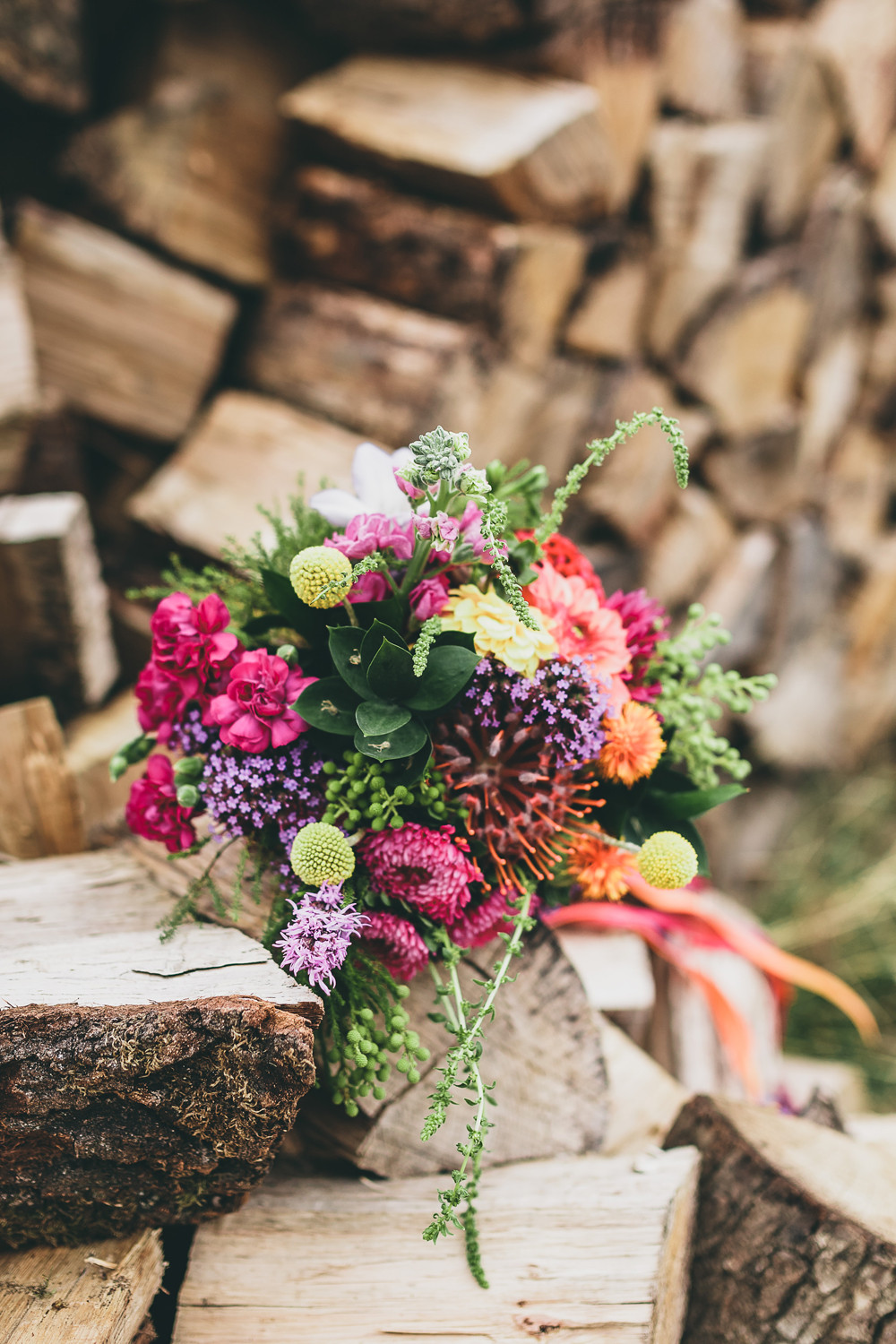 Colourful DIY wedding bouquet on a pile of rustic logs