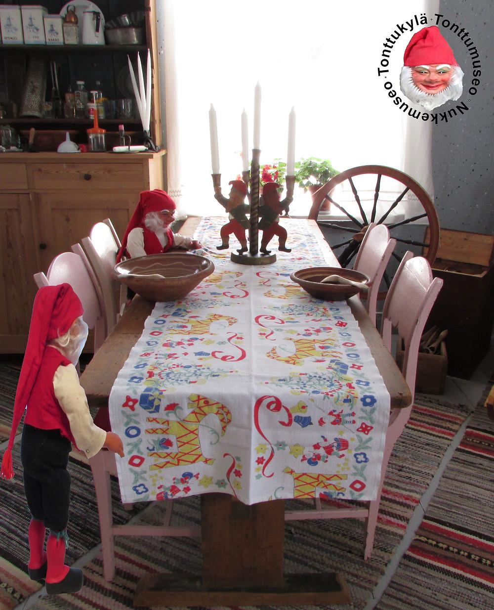 Talonpoikais kynttilänjalka, tonttuukko kynttilänjalka, lankkupöytä, vanhat tuolit, tupakeittiö, räsymatot, rukki, puulaayikko, lautashylly, savivati, puulusikka