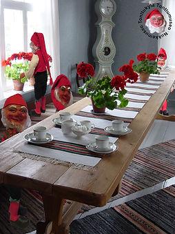 Isotupa Tonttukylässä, tontut pöydän ääressä, Arabian vanhat kahvikupit, kaappikello, suutarinlamppu, pelargonia, räsymatto, roiskemaalaus, tuvanikkuna, vanha tupa, vanha tuoli, tuvanpenkki, penkki, lankkupöytä, maalaistalo, maaseutu,