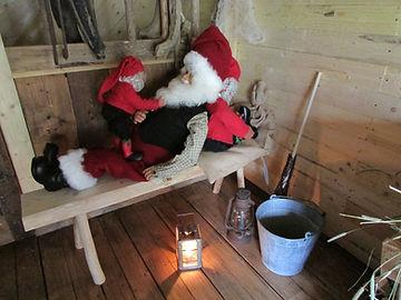 Tonttu vetää joulupukin parrasta, lattialla pläkkiämpäri, vanha tallilyhty ja luuta