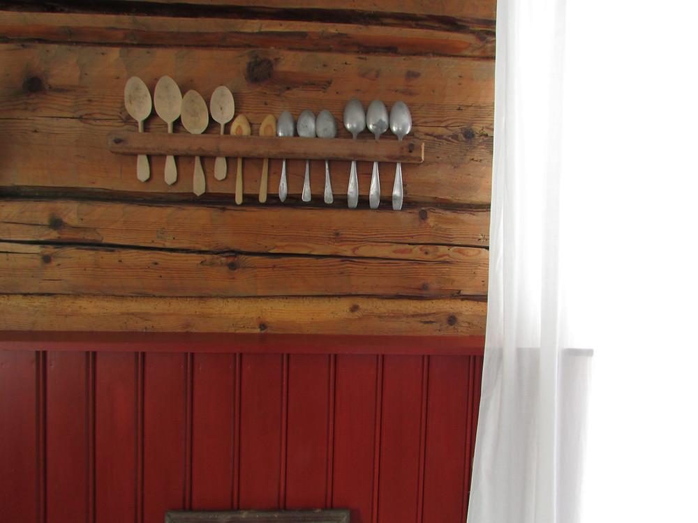 Lusikkahylly, vanhat lusikat, hirsiseinä, helmipaneli, punainen seinä, lakanaverhot, lautahylly, tupakkahylly