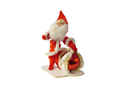 Joulutonttu pitelee joulupalloa, vanha joulukoriste piipunrassista
