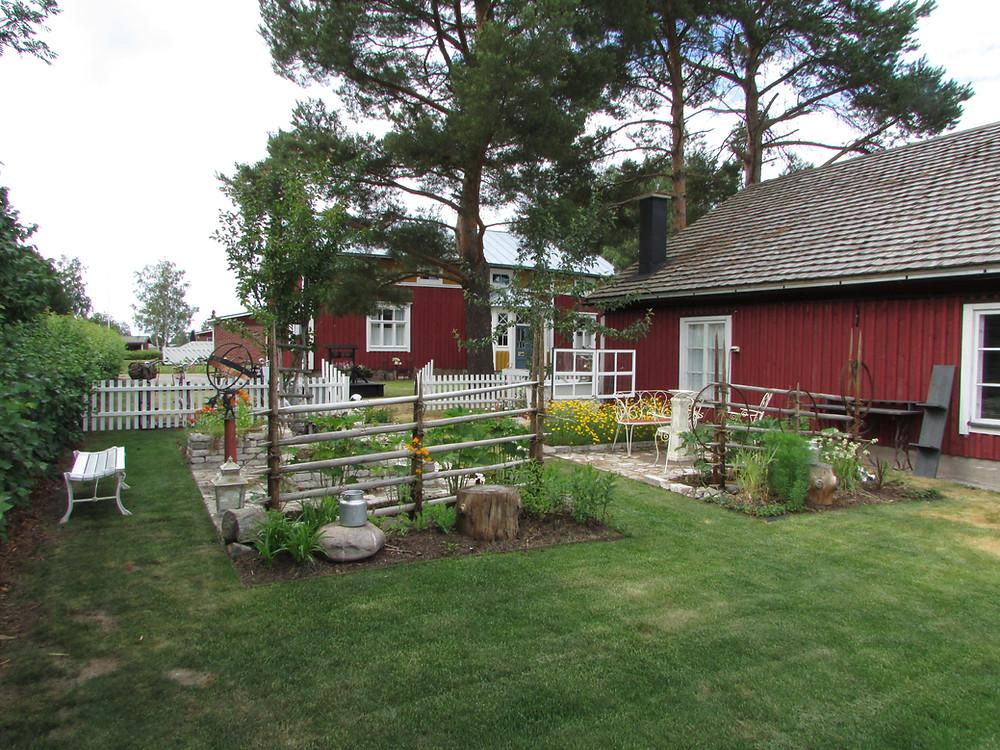 Siirtonurmikko, vanha piha, vanha talo, aita, paanukatto, ulkorakennus, pihapuut, puutarhatuolit, valurautainen penkki, aurinkokello, puutarhapenkki