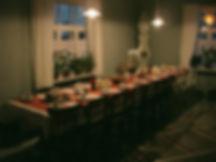 Syysretki Tonttukylään, lankkupöytä, vanhat ikkunat, suutarinlamppu, kaappikello, vanha tuoli, räsymatot, kynttilät, pitsiverho, lankkulattia