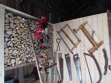 Tontut liiterissä kiipeileevät tikapuilla. Liiterin seinällä vanhoja sahoja, Purmo poka, pistosaha ja tukkimitta