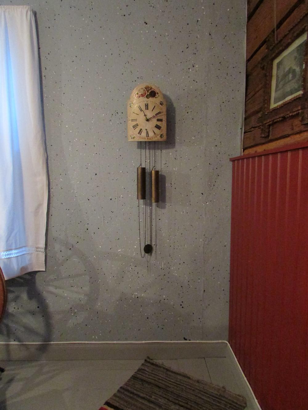 Tuvankello, kukkakoristeinen kello, punnuskello, roiskemaalatut seinät, hirsiseinä, isotupa, pirtti, rukki, räsymatto