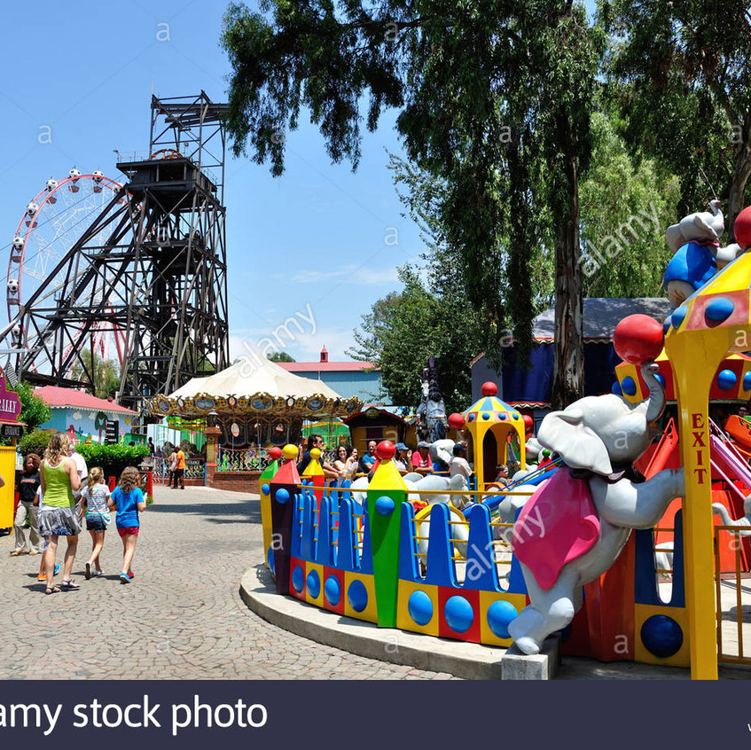 coal-winding-gear-and-childrens-rides-at-gold-reef-city-theme-park-CF4P9W