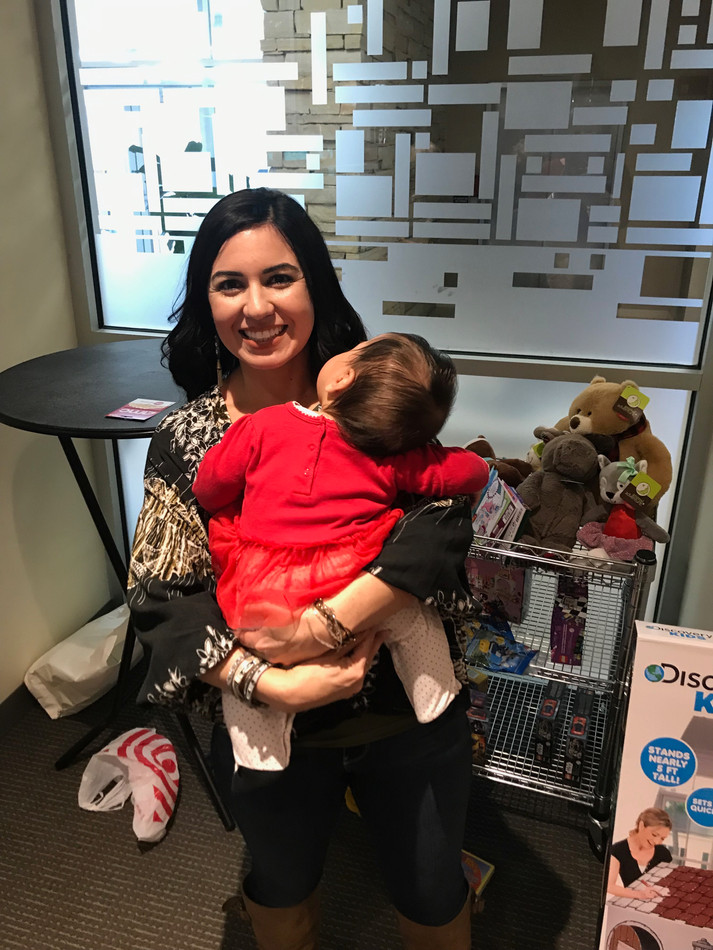 Nicole, a Max's Treehouse board member, holds a sleeping baby while her older siblings do their gift shopping.