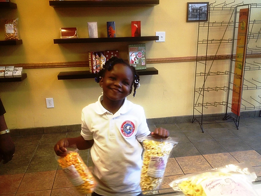 Little Girl holding 2 bags of popcorn