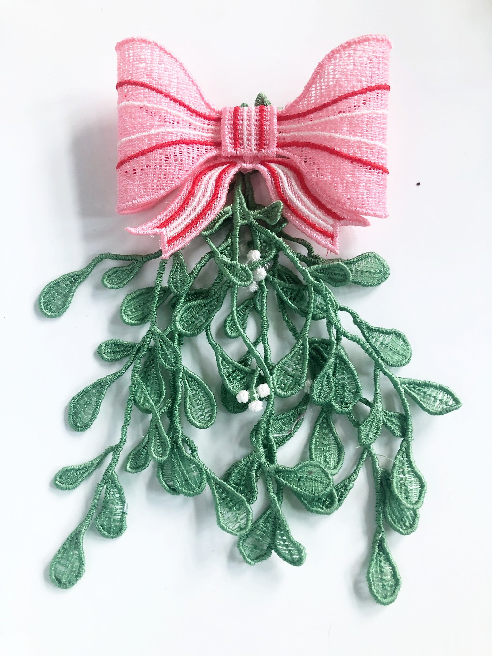 cute freestanding lace mistletoe with a pink bow on a white background
