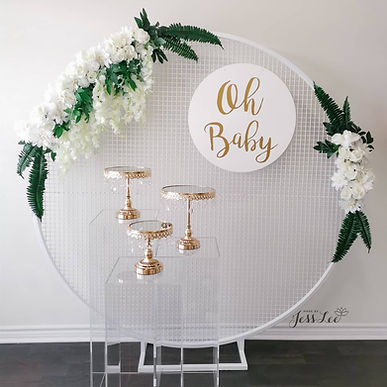 Round mesh backdrop with faux florals, clear plinths, cake stands, and custom signage