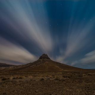 """Ночной вид Пику-ду-Венту (""""пик Ветра"""") и несущиеся над пустынным ландшафтом облака, остров Сан-Висенти  A nocturnal view of Pico do Vento ('Wind's Peak') and clouds fying over a desert landscape, São Vicente island"""