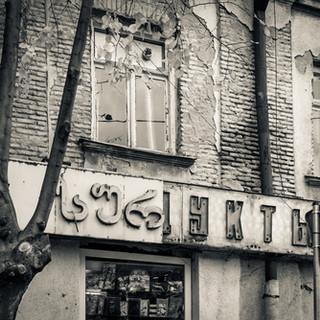 Надпись на русском выглядывает из-под отвалившихся грузинских букв на вывеске, район Авлабари Cyrillic letters in a grocery signboard peep out from fallen Georgian ones, Avlabari neighbourhood