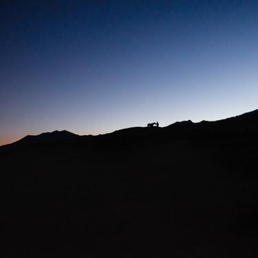 Горный гребень, человек и лошадь на послезакатном фоне  A mountain ridge, a man, and a horse at the after-sunset background