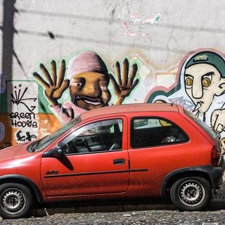 Маленькая красная машинка на улице Little red car parked in a street