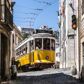 Знаменитый лиссабонский трамвай маршрута №28 на узких кривых улочках района Альфама The famous Lisbon's route 28 tram in curved and narrow streets of Alfama